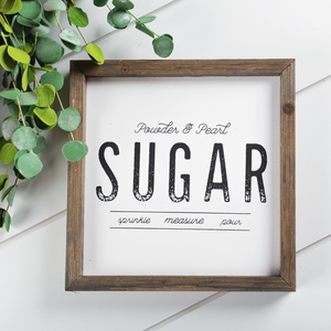 "Kneaders barn box sign with rustic wood frame and ""Powder & pearl sugar, sprinkle, measure, pour"" in distressed black text."