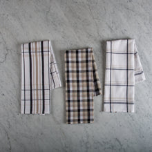 Set of three plaid woven 100% cotton tea towels folded on a marble surface
