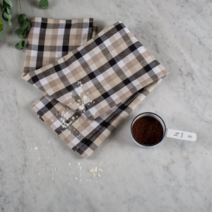 Black, white, and tan plaid woven 100% cotton tea towel on a marble surface with a tin measuring cup.