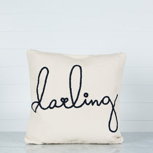 "Cotton oversized square pillow with ""darling"" black embroidery on a marble surface with a shiplap background."