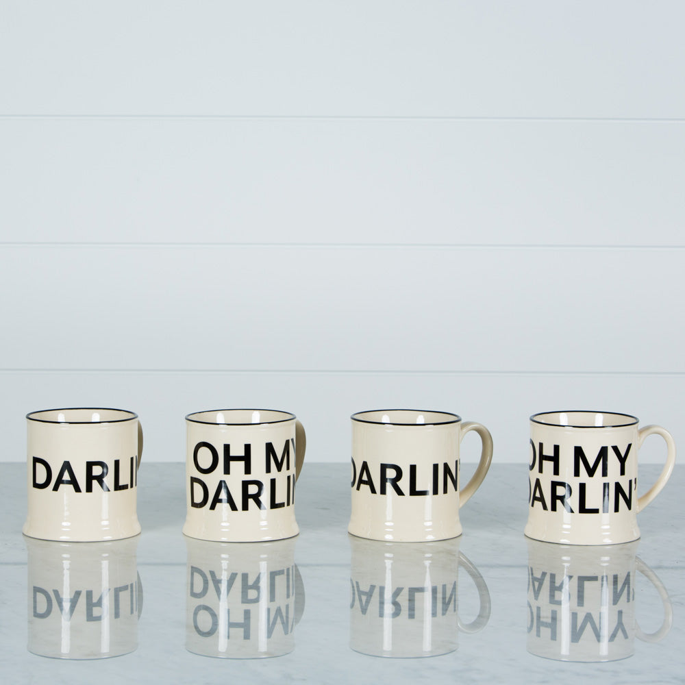 Four Oh My Darlin cream stoneware mugs on a marble surface.