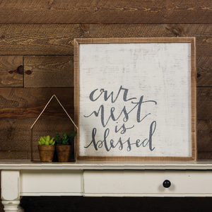 "White sign with a light wood frame with ""our nest is blessed"" stamped in grey cursive font."