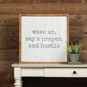 "White sign with a light wood frame with ""wake up, say a prayer, and hustle"" stamped in grey typewriter font."