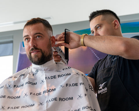 Claudio Ferreira cuts hair at the Reebok headquarters representing Fade Room Barbershop
