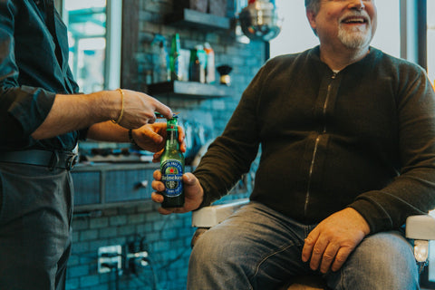 Claudio the barber giving a Heineken 00 to one of his clients at Fade Room barbershop