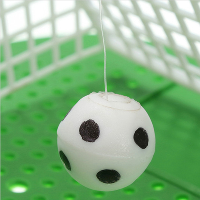 Ball dangling in front of soccer goal urinal mat