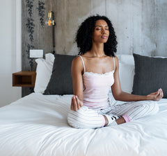 Woman on a bed in lotus pose