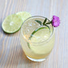 In a round tumbler, a light colored cocktail poured over ice with lime wheel garnishes.
