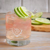 A Heritage Distilling Co. branded tumbler filled with a very light pink colored cocktail that is filled to the top with ice. A metal stir stick is place over top of the drink with three lime wedges over it. There are also more limes in the background.