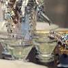 Silver party decor and fancy stemless martini glasses full of a HDC Citrus Vodka and HDC Blood Orange Vodka-based drink.