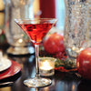 A beautiful table setting with crystal vases and candles. A HDC Pomegranate vodka-based cocktail drink in a stemmed martini glass.