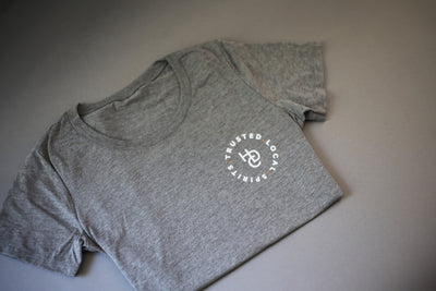 "An HDC light grey tshirt with the HDC logo and ""trusted.local.spirits."" on it in white lettering."