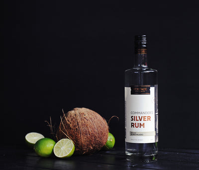 A 750ml bottle of HDC Commander's Silver Rum next to a coconut and some limes.