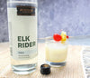A 750ml bottle of HDC Elk Rider Vodka and a tropical cocktail with fruit garnishes.