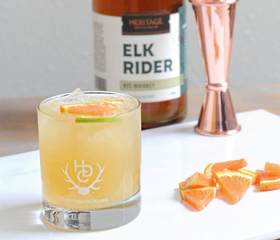 A 750ml bottle of Elk Rider Rye Whiskey and a cocktail in a rocks glass.