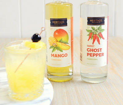 A 750ml bottle of HDC Mango Vodka and a 750ml bottle of Sweet Ghost Pepper Vodka. Both spirits combined are used to make the Sweet Heat Cocktail (that is pictured).
