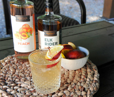 A 750ml bottle of HDC Peach Vodka and a 750ml of HDC Elk Rider Bourbon with a Peaches and Bourbon Cocktail.