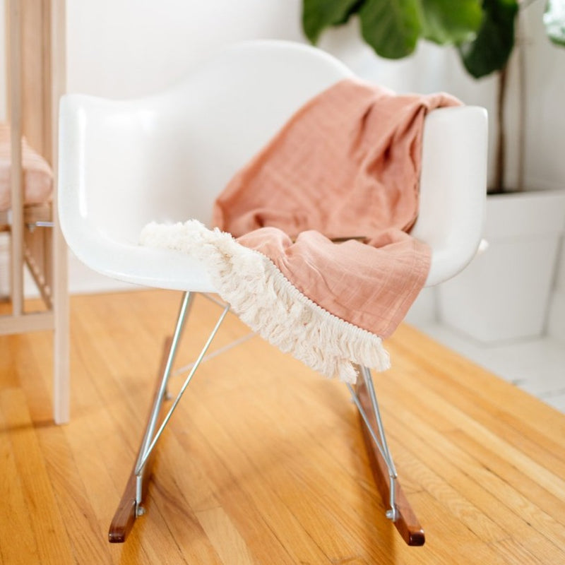 pink fringe blanket on rocking chair