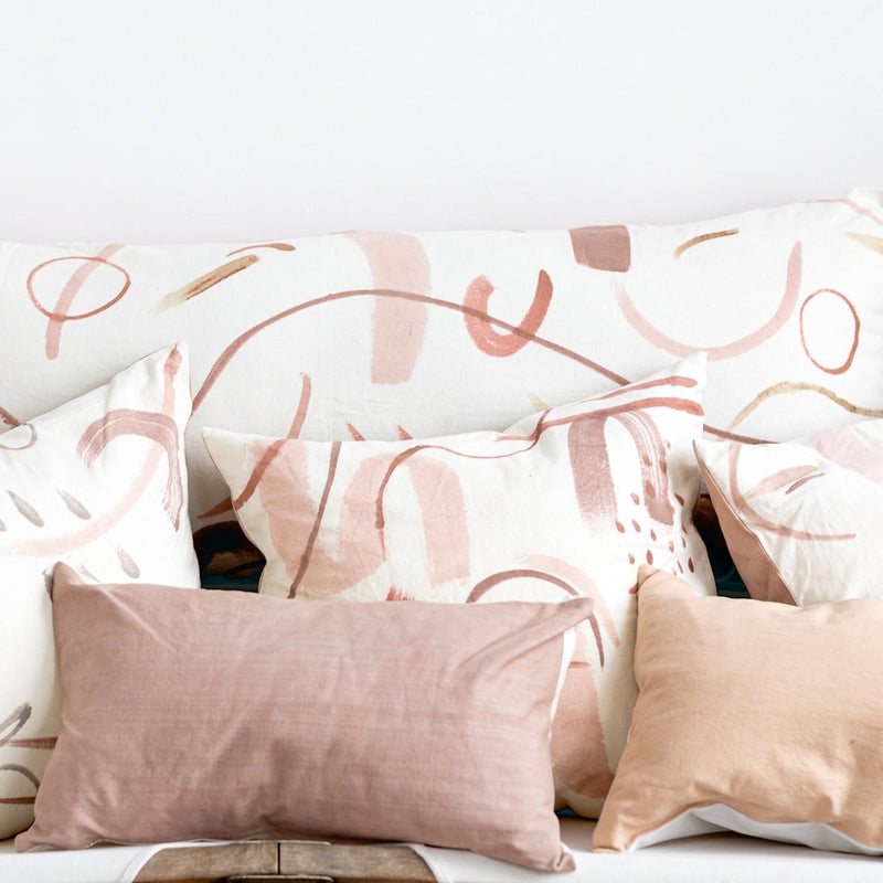 pile of hand painted and solid pink pillows