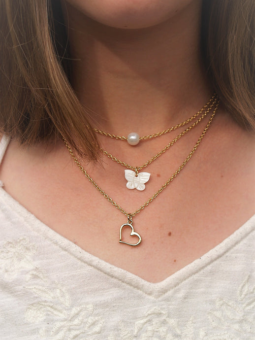 Layered gold chain necklace with pearl, heart, and butterfly