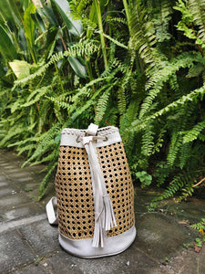 These rattan handbags are hand woven and then smoked over a coconut husk as part of the drying process to attain their natural golden color.