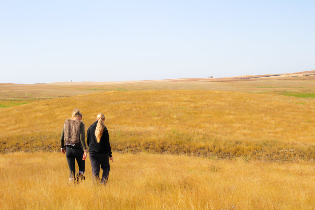 two women walking in a pasture in Saskatchewan Photography by Georgina Sonmor