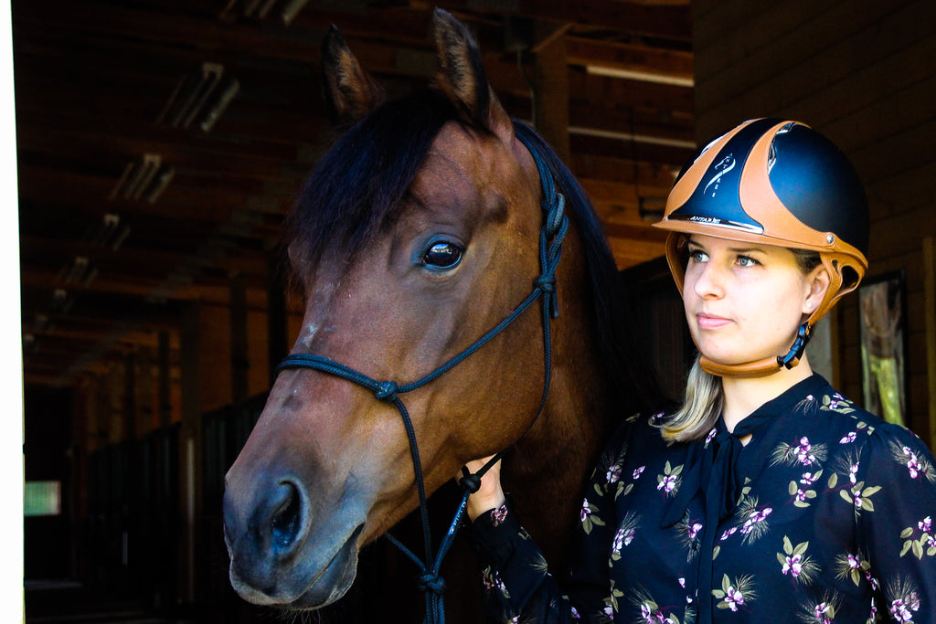 horse and woman with helmet standing looking into the distance