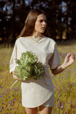 Model wearing the Nori Top while in a field
