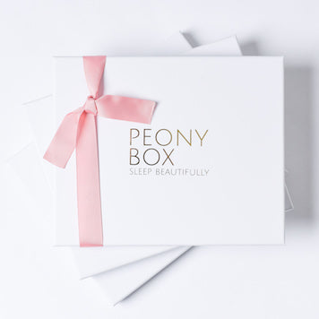 Peony Box gift box with tied pink ribbon and a silk pillowcase inside