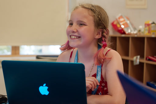 Girl smiling at laptop computer