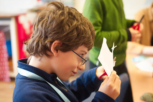 Boy cutting out paper shapes