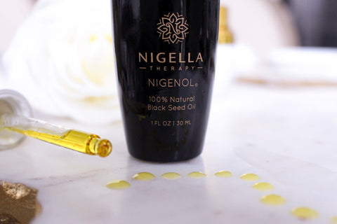 A bottle of Nigenol, 100% Natural Black Seed Oil with drops of the oil on the counter