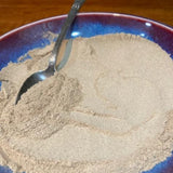 ashwagandha root powdered in a blue bowl with a spoon