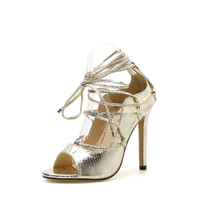 Roman style gold serpentine cross-strap sandals with high heels