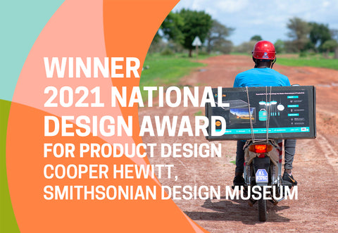 Man riding motorbike with BioLite SolarHome 5000 attached to back, text overlay announcing BioLite is the winner of the 2021 National Design Award