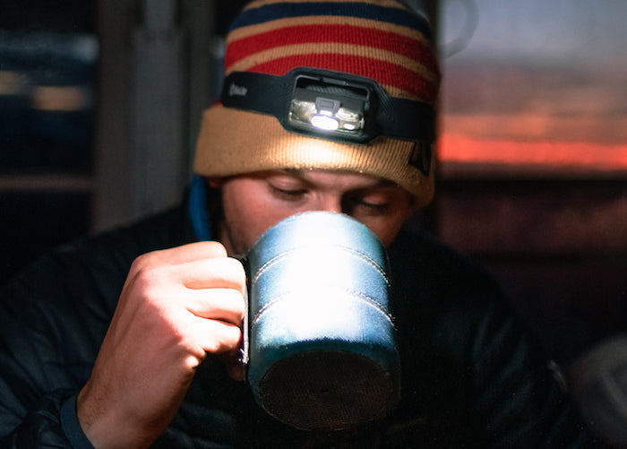Man drinking coffee at sunrise with BioLite Headlamp