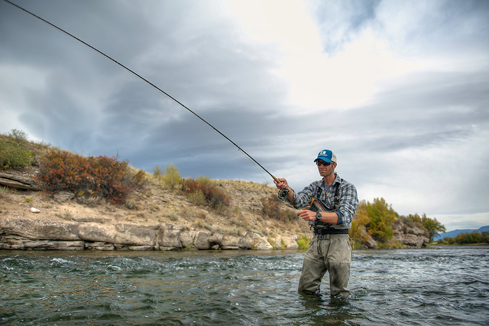 Guy in flannel fly fishing