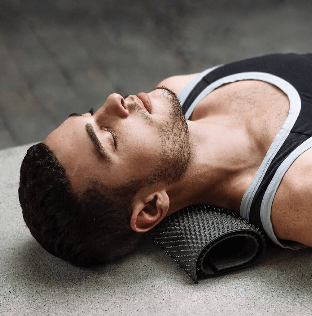 Man usng Aku Mat for acupunture for neck pain - Image