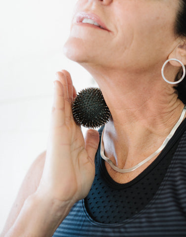 Women Using Aku Ball as acupunture for neck pain - Image