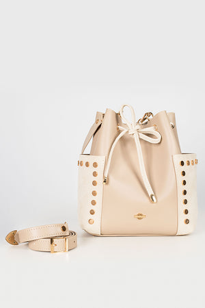 A white bucket bag from the front view with a detachable strap on the left