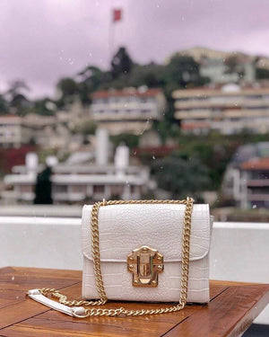 A white handbag placed on a table on a balcony with the city behind.