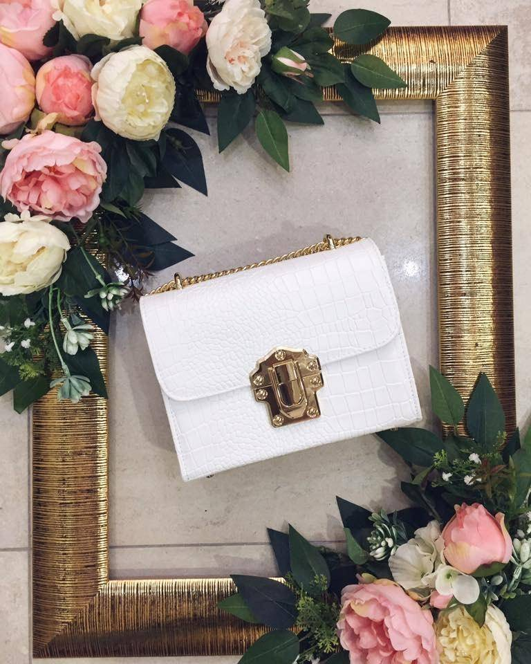 A white handbag placed on a picture frame surrounded by flowers.