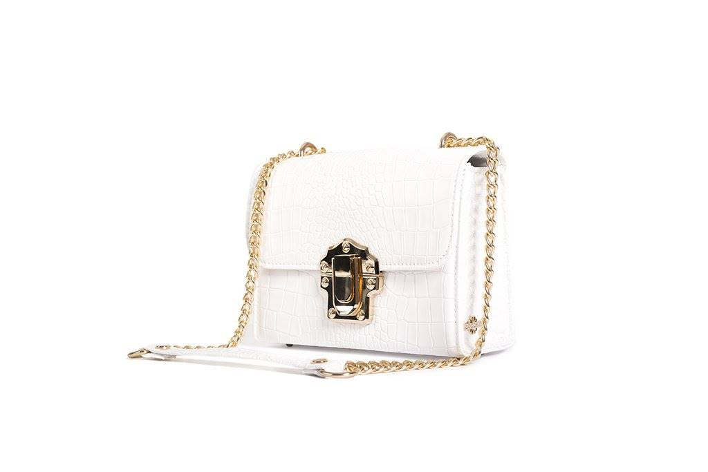 A white handbag from the front with the strap placed in front.