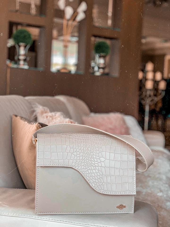 A beige handbag placed on the side of the couch in a room.