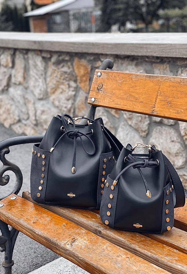 Two bucket bags on a park bench