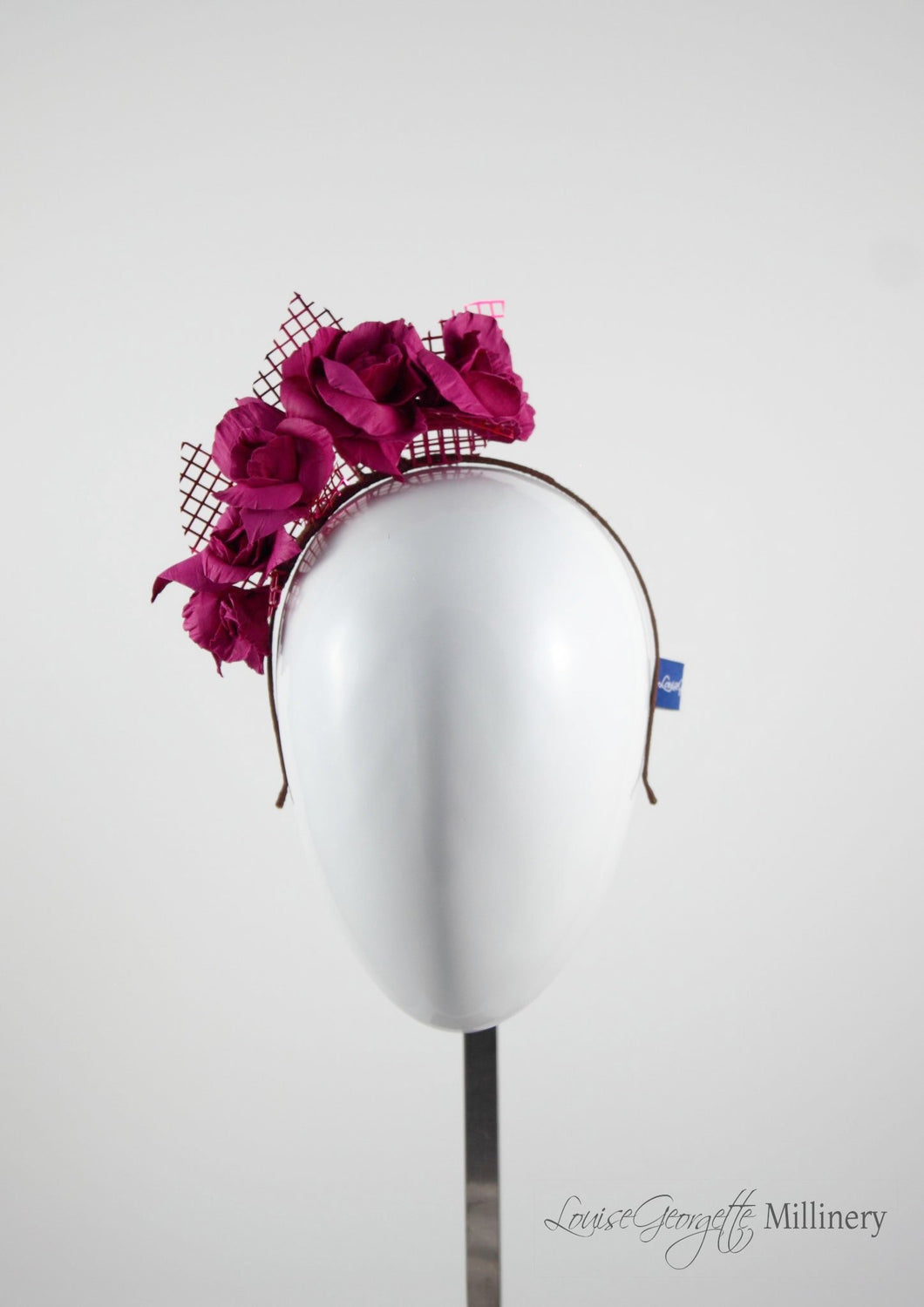 Leather roses on headband with reflective lattice detail. Millinery handmade in London. Front view. Pink