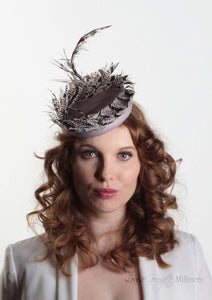 Victoria Pillbox hat with leather base and Lady Amherst feather. Model front view.  Millinery handmade in London.