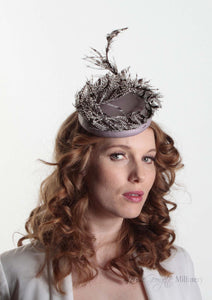 Victoria Pillbox hat with leather base and Lady Amherst feather. Model side view.  Millinery handmade in London.