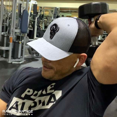 BRANDON DINOVI wearing a RAM ADVANTAGE PURE ALPHA t-shirt and premium HEATHER GREY and BLACK 3D embroidered TRUCKER HAT while working out his BICEPS