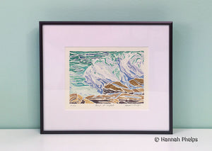 Framed white-line woodcut print of a wave crashing on rocks in Maine by New England artist, Hannah Phelps